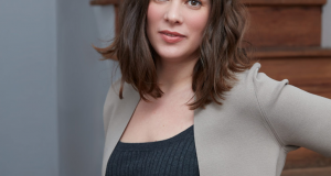 A headshot of playwright Mathilde Dratwa. She is standing in front of a stair case. Her hand is resting on her hip.