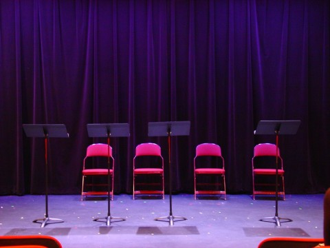 Four music stands and four chairs on the Playwrights' Center's stage.