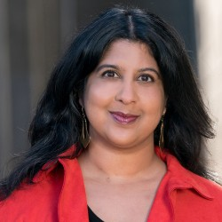 A headshot of Amarita Ramanan. She wears an open red shirt with a black shirt underneath. She has a partial smile as she looks directly at the camera.