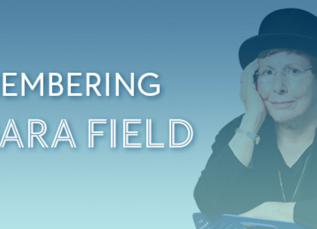 A light blue box with the words REMEMBERING BARBARA FIELD on it. An image of Barbara is to the left of the text. She is sitting in a chair, wearing a black shirt and hat. Her right hand rests on her face. Her left hand rests on the chair.