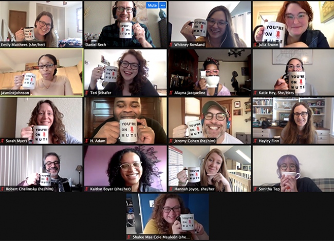 """A screen cap of a Zoom meeting. Many staff members are holding coffee mugs next to their face. The mugs have text on them. """"You're on Mute"""""""