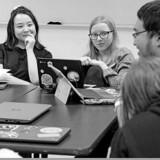 A group of students sit around a table, discussing ideas with each other. Laptops are in the foreground of the image.